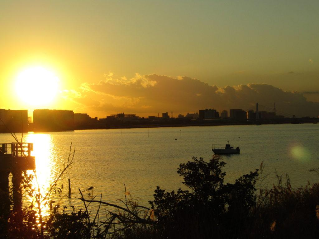 羽田空港の敷地内のソラムナード羽田緑地から見た多摩川と夕日です。
