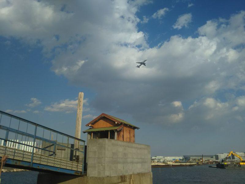 大田区羽田の五十間鼻の無縁仏堂の上を新飛行ルートの飛行機が飛んでいきます。